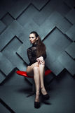 Fashionable model sitting in a red chair Royalty Free Stock Photography