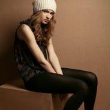 Fashionable model sitting on wooden cube Stock Photo