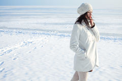 Fashionable model in white coat near winter sea Royalty Free Stock Photo