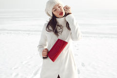 Fashionable model in white coat near winter sea Royalty Free Stock Images