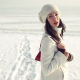 Fashionable model in white coat near winter sea Stock Photo