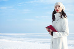 Fashionable model in white coat near winter sea Royalty Free Stock Image
