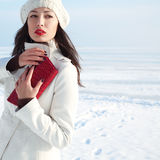 Fashionable model in white coat near winter sea Royalty Free Stock Photos