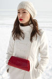 Fashionable model in white coat near winter sea Stock Photography