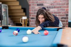 Portrait of pretty young woman playing billiards royalty free stock photos