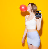 Fashionable modern girl posing in colorful top and skirt inflates the red bubble from chewing gum and with a vintage camera in her. Fashionable modern posing in Stock Images
