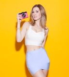 Fashionable modern girl posing in colorful top and skirt with a vintage camera in her hand a yellow background in the studio. Look Stock Images