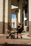 Fashionable modern mother on a city street with a pram Stock Images