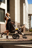 Fashionable modern mother on a city street with a pram. Young mo Stock Images