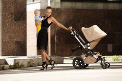 Fashionable modern mother on a city street with a pram. Young mo Royalty Free Stock Photography