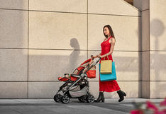Fashionable modern mother on a city street summer Stock Photos