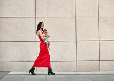 Fashionable modern mother on a city street Royalty Free Stock Photo
