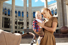 Fashionable modern mother on a urban street with a pram. Young m Royalty Free Stock Image