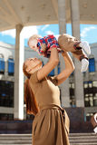 Fashionable modern mother on a urban street with a pram. Young m Royalty Free Stock Images