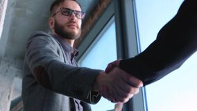 Fashionable modern young man with beard businessman shaking hands with partner. Have concluded a deal or contract. Located in a modern office in the loft style stock footage