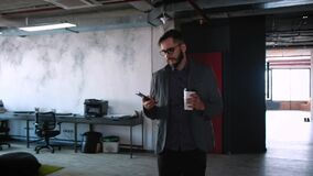 Fashionable modern young man with beard businessman walking along modern office in loft style. In the hands of a glass stock video