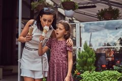 Fashionable mother and cute daughter enjoy ice cream on a hot summer day. Fashionable mother and cute daughter enjoy ice cream on a hot summer day, standing Royalty Free Stock Photo