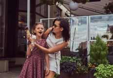 Fashionable mother and cute daughter enjoy ice cream on a hot summer day. Fashionable mother and cute daughter enjoy ice cream on a hot summer day, standing Stock Photo