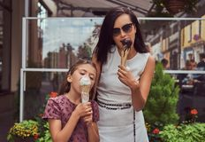 Fashionable mother and cute daughter enjoy ice cream on a hot summer day. Fashionable mother and cute daughter enjoy ice cream on a hot summer day, standing Royalty Free Stock Photography