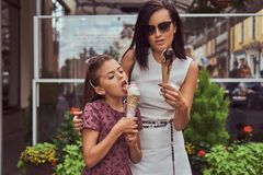 Fashionable mother and cute daughter enjoy ice cream on a hot summer day. Fashionable mother and cute daughter enjoy ice cream on a hot summer day, standing Stock Image