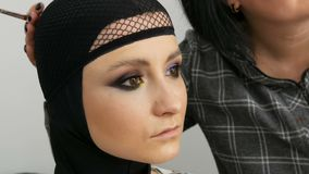 Fashionable multi-colored eye shadow chameleon with yellow purple gray silver color on the eyelid of beautiful girl. Fashionable multi-colored eye shadow stock video footage