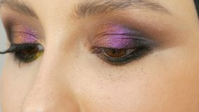Fashionable multi-colored eye shadow chameleon with yellow purple gray silver color on the eyelid of beautiful girl stock footage