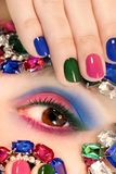 Fashionable multi-colored manicure short nails and makeup royalty free stock photos