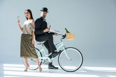 Fashionable multicultural couple with glasses of champagne. And retro bicycle royalty free stock photography