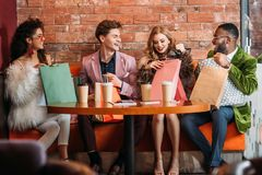 Fashionable multiethnic young people looking into paper bags while drinking coffee together royalty free stock image
