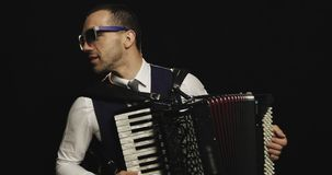 A fashionable musician in a white shirt plays the accordion in the studio on a black background. stock video