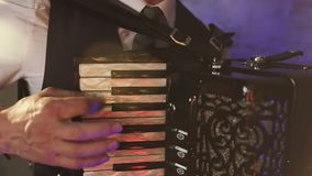 A fashionable musician in a white shirt plays the accordion in the studio. stock video