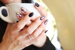 Fashionable nails - nail art - beauty skin treatment advertisement. Hands holding hot coffee royalty free stock photo