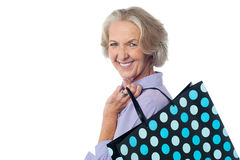 Fashionable old lady with shopping bag. Stylish old woman holding polka shopping bag Stock Image
