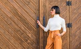 Fashionable outfit slim tall lady. Fashion and style concept. Woman walk in elegant outfit. Woman fashionable brunette. Stand outdoors wooden background. Girl royalty free stock images