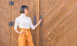 Fashionable outfit slim tall lady. Fashion and style concept. Woman walk in elegant outfit. Woman fashionable brunette. Stand outdoors wooden background. Girl royalty free stock photo