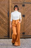 Fashionable outfit slim tall lady. Fashion and style concept. Woman walk in loose pants. Woman fashionable brunette. Stand outdoors wooden background. Girl with royalty free stock photos