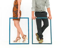 Fashionable people. Cropped view of men and women legs behind two empty frames, on white background royalty free stock images