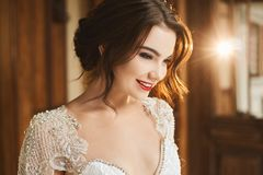 Fashionable photo of beautiful smiling young brunette woman in lace dress. Happy bride, wedding preparation stock images
