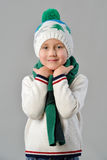Fashionable Portrait of a adorable toddler boy in warm winter hat and scarf on grey background Stock Photography
