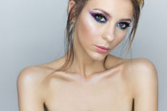 Fashionable portrait of a beautiful sexy girl with crazy hairstyle with bright colored makeup with bared shoulders in the studio o Stock Photography