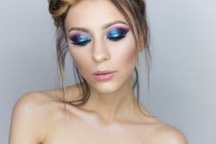 Fashionable portrait of a beautiful sexy girl with crazy hairstyle with bright colored makeup with bared shoulders in the studio o Royalty Free Stock Image