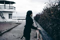 Fashionable portrait of a young brunette woman in black clothes, jeans T-shirt, coat and sunglasses, in a Gothic style sad mood stock photography