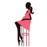 Fashionable pregnant woman sitting on the bar chair Royalty Free Stock Photos