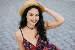 Fashionable pretty brunette female with make-up wearing straw hat on head and summer dress smiling pleasantly into camera while po. Sing outdoors. Happy stock photos