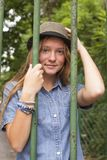 Fashionable pretty girl in the park behind the fence. Travel. Royalty Free Stock Photography