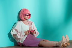 Fashionable pretty girl in pink wig sitting on floor. And using joystick stock image