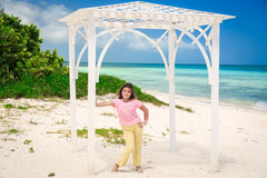 Fashionable pretty  styled smiling little girl standing inside open air gazebo at Cuban beach Royalty Free Stock Photo