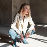 Fashionable pretty young sexy woman in a stylish leather jacket with metal rivets in ripped jeans in cowboy boots sits. On a sunny spring day indoors royalty free stock photos