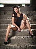 Fashionable pretty young woman with long legs sitting on old stone stairs. Beautiful long hair brunette on high heels shoes posing. Provocatively. Young model royalty free stock photo