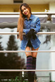 Fashionable pretty young woman wearing blue jeans, and long striped knee socks Stock Image
